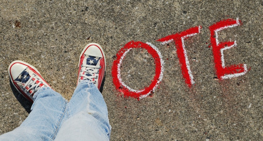 A pair of feet make making a V next to the letters O, T, E written in chalk, spelling the word vote